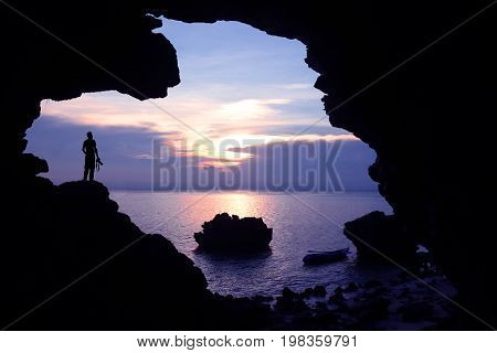 Photographer in front of the cave near the sea with kayaking and purple sky sunset.