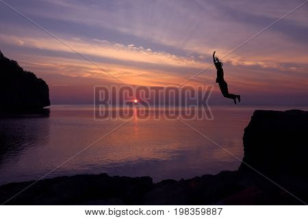 Asian girls jump from a cliff into the sea episode sunset Somersault to the ocean