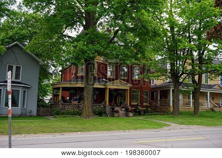 CADILLAC, MICHIGAN / UNITED STATES -  MAY 31, 2017: A red brick home with a wraparound porch in Cadillac's Courthouse Hill Historic District.