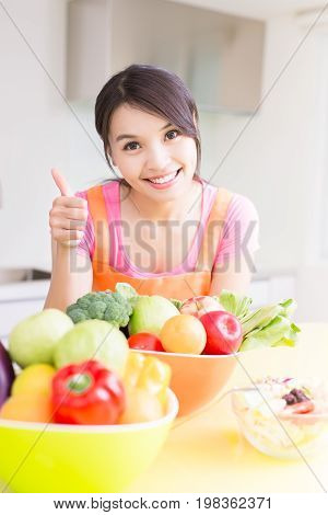 beauty housewife smile happily and show thumb up in the kitchen