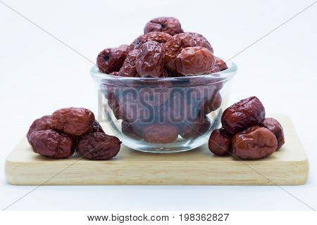 Red chinese dry jujube on wooden board on white background
