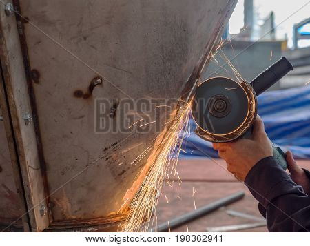 Angle grinder in use at a mechanical workshop.