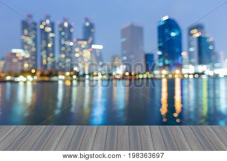Opening wooden floor Twilight blurred bokeh light city office building with reflection abstract background