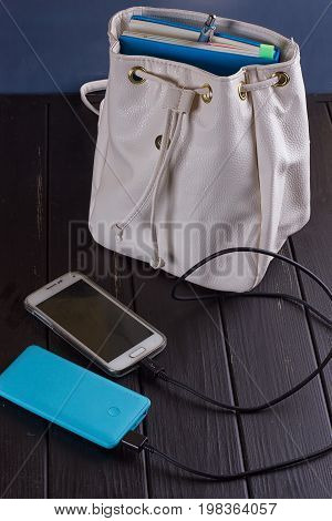 white smartphone is charged from a powerbank near a backpack on a black wooden background