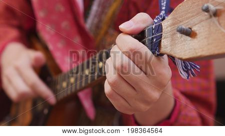 Girl in Russian folk costume playing the balalaika, close up