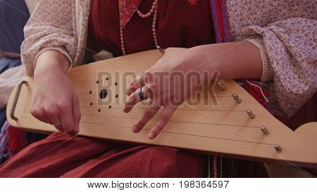 Girl in Russian folk costume playing vintage musical instrument - the gusli, close up