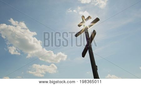 Wooden orthodox Cross in front of blue sky - telephoto