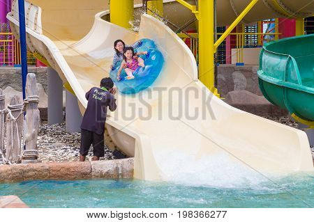 Phuket Thailand - 8 July 2017 - couple of asian tourists mother and daughter is photographed while happily riding down a water slider ride at Splash Jungle water theme park in Phuket Thailand on July 8 2017.