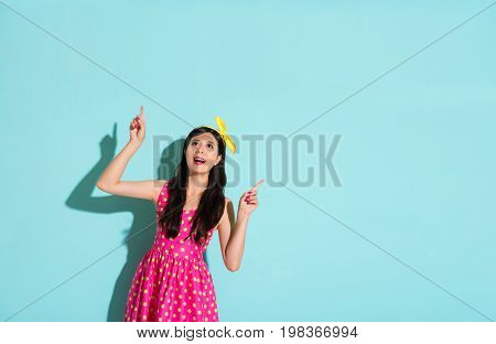 Chinese Woman Pointing To The Top Blue Background