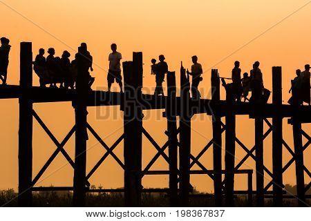 Silhouette fo people walking at U Bein Bridge Mandalay Myanmar