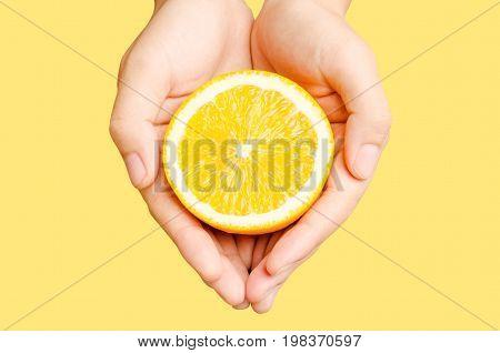 Half of Navel orange fruit holding by hand isolated on orange background