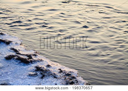 Sunlight reflection and wrinkles on stream in winter aura.