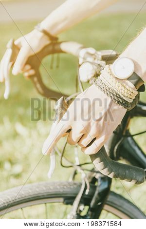 Male hands holding handlebar of bicycle in summer outdoor close-up.
