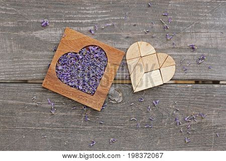 Lavender in wooden heart-shaped box and tangram puzzle in heart shape on wooden background