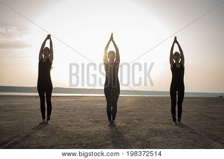 three young women practicing yoga poses and asanas. Partner yoga, acrobatic yoga. Yoga class in black wear training in desert during sunset