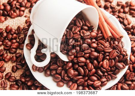 The white cup with a white saucer is overturned with coffee beans and cinnamon on sacking. Top view close-up