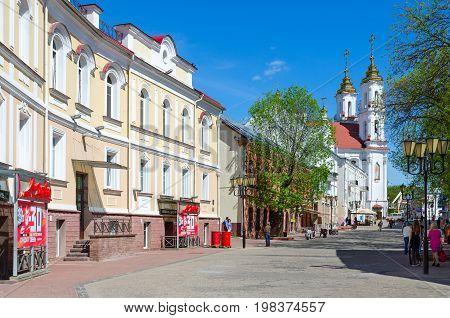 VITEBSK BELARUS - MAY 23 2017: Tolstoy Street with view of Holy Resurrection (Rynkovaya) Church Vitebsk Belarus. Unknown people walking down street