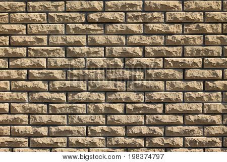 Background of yellow relief facing bricks. Bricks relief.