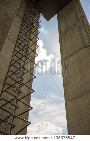 modern belfry with metal stairs and cloudy blue sky