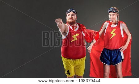 Two funny men in suits of superheroes. Thin and fat people.