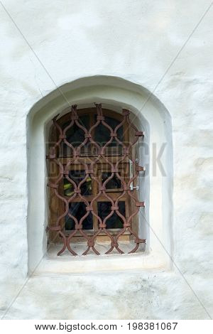 one 1 small window with bars glass white wall medieval building