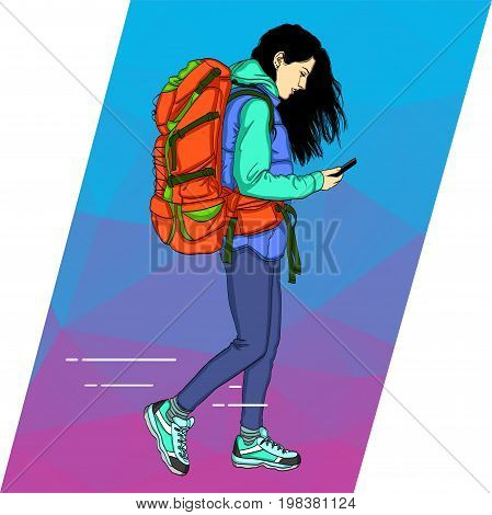 Young woman is walking with a mobile phone. A beautiful girl with her hair in loose clothes and in casual clothes, with a large backpack