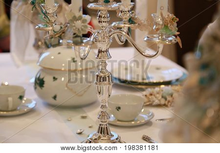 Tableware and candle stand on the table