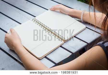 Human pick the blank note book .