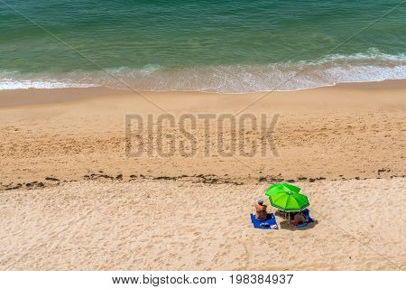 Couple on beach under parasol. Albufeira Portugal - July 18 2017: A couple laying on a beach sunbathing at the Algarve coast Portugal. Seen from above. Getting some shade with parasols.