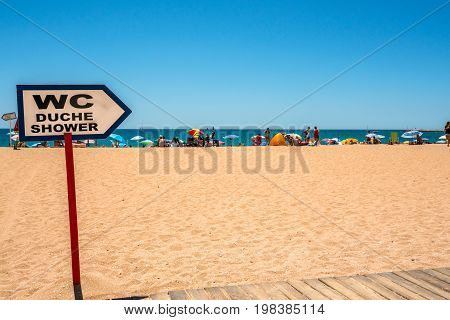 WC sign and people on sandy beach. Albufeira Portugal - July 19 2017: Beach at the Algarve coast with tourists sun bathing with sun parasols. In the foreground a sign showing the direction to WC and showers.