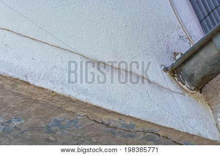 Small cracks in the plaster on the outer wall caused by a tree bend.