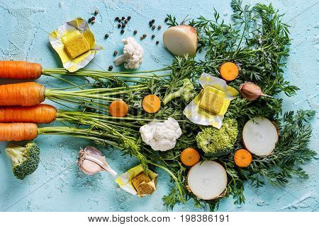 Raw vegetables and bouillon cubes for cooking soup. Young carrot with haulm, broccoli, cauliflower, onion, garlic, salt pepper over turquoise concrete background. Top view. Dinner cooking concept