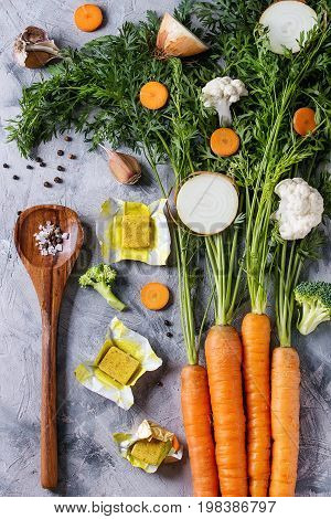 Raw vegetables and bouillon cubes for cooking soup. Young carrot with haulm, broccoli, cauliflower, onion, garlic, salt, pepper, spoon over gray concrete background. Top view. Dinner cooking concept