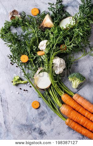Raw vegetables for cooking soup. Ingredients young carrot with haulm, broccoli, cauliflower, onion, garlic, salt pepper over gray concrete background. Top view. Dinner cooking concept