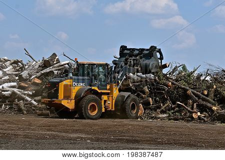 MOORHEAD, MINNESOTA, July 27, 2017: The 644 John Deere front end loader  moving tree residue is a product of the John Deere Co, an American corporation that manufactures agricultural, construction, forestry machinery, diesel engines, and drivetrains.