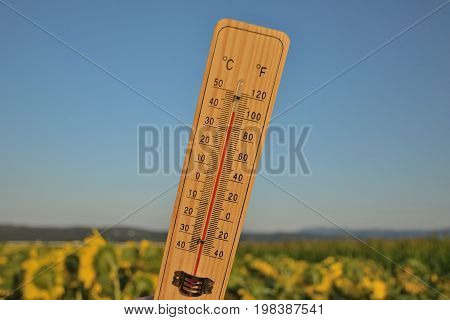Mercury wooden thermometer shows very high temperature. Temperatures in Celsius and Fahrenheit degrees. Hot summer weather. Forty degrees over zero during the day.