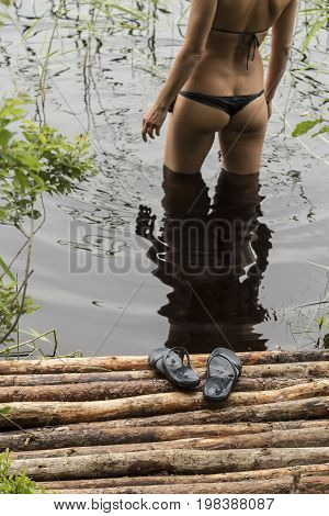 Cute woman cautiously enters the clean forest lake leaving the slippers on a makeshift bridge of sticks.