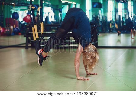 Core body exercise concept. Woman exercising with suspension straps in gym.