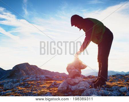 Alone Adult Man Is Stocking Stone To Pyramid.alps Mountain Summit, Evening Sun At Horizon.