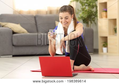 Front view of a fitness woman holding a water glass watching on line tutorials sitting on the floor in the living room at home