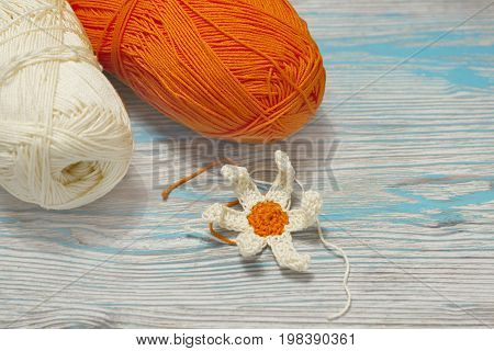 Cotton yellow and orange yarn for knitting crochet. The beginning of bright flower. Colorful original crochet handmade craft work with flower. Homemade creative craft