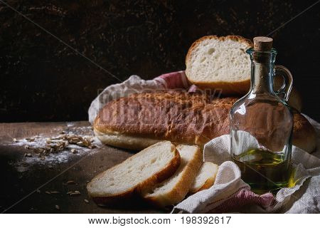 Homemade white wheat bread whole and slice served with bottle of olive oil and wheat grain seeds on white linen towel over dark wooden kitchen table. Rustic style.