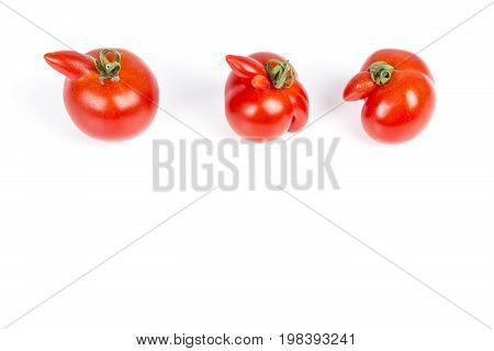 Deformed aberrant abnormal anomalous red tomatoes on a white background. Deformation due to cold weather during ovulation. Strange forms grown mutated tomato.