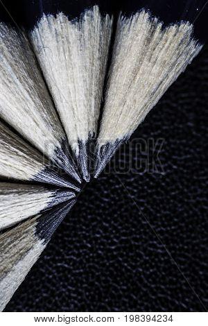 Several black pencil tips on black background