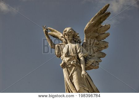 An angel statue with arm raised under a blue sky.