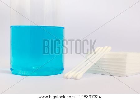 cotton buds and bandage with blue alcohol for medical in the plastic bottle on white background