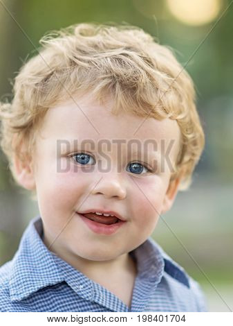 Close-up portrait of beautiful little baby boy smiling and looking to camera at summer day