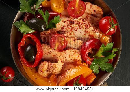 Fresh Vegetables and Chicken. Fried chicken fillet and vegetables tomato garlic onion bell pepper basil green and spicy seasoning in cooking pan. Healthy dinner at Restaurant. Closeup top view
