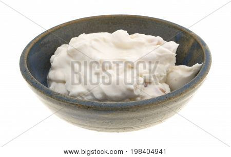 Large portion of apple vanilla Greek yogurt in an old stoneware bowl isolated on a white background.