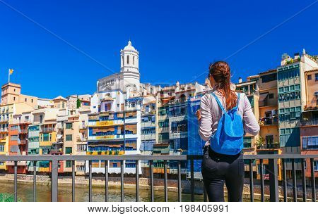Tourist Woman See On Colorful Red And Yellow Houses And Bridge River Onyar In Girona, Catalonia, Spa